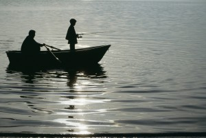 Father with son (10-11) in small boat fishing
